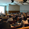 A speaker lectures to a crowded conference room.
